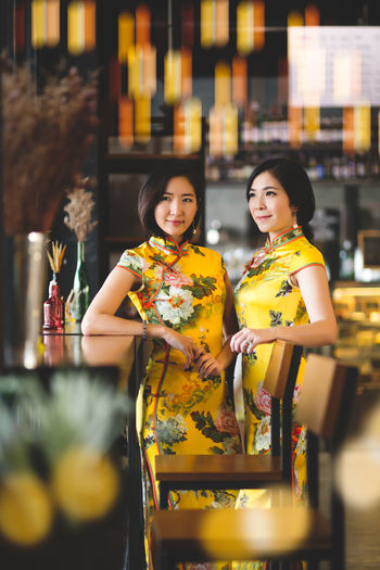 Women Smiling Two People Emotion Young Adult Young Women Three Quarter Length Adult Happiness Indoors  Yellow Front View Looking At Camera Selective Focus Togetherness Portrait Lifestyles Beautiful Woman People Food And Drink Qipao Chinese New Year Holiday