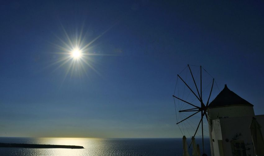 Oia Santorini Greece Windmill Against The Sun Sun Sea Water Lens Flare Travel Destinations Outdoors Sky Sunlight Horizon Over Water Sunbeam Tranquility No People Tranquil Scene Silhouette Windmill Clear Sky Blue