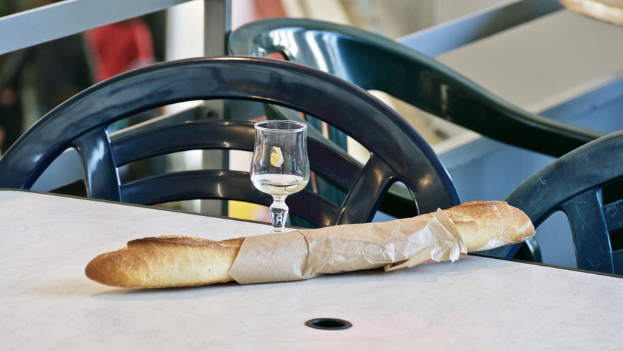 Close-up of baguette with drinking glass on table
