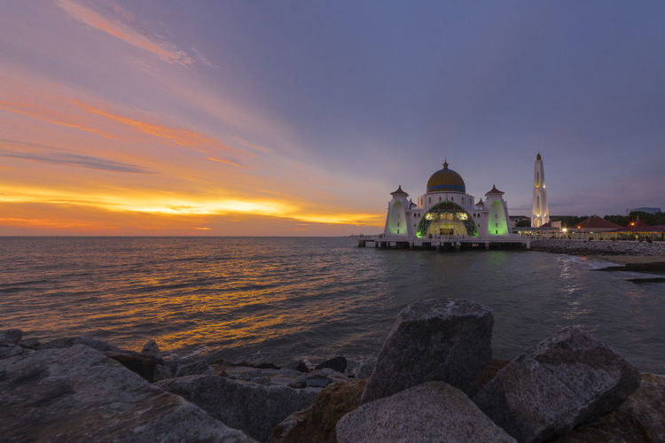 A beautiful sunset at the Malacca Straits Mosque or Masjid Selat Melaka in Malacca, Malaysia Beach Beautiful Building Exterior Cultures Faith Golden Hour Illuminated Illuminated Buildings Islam Islamic Architecture Islamic Art Magenta Malaysia Masjid Minaret Mosque Place Of Worship Religion Rock Twilight Sky Waters