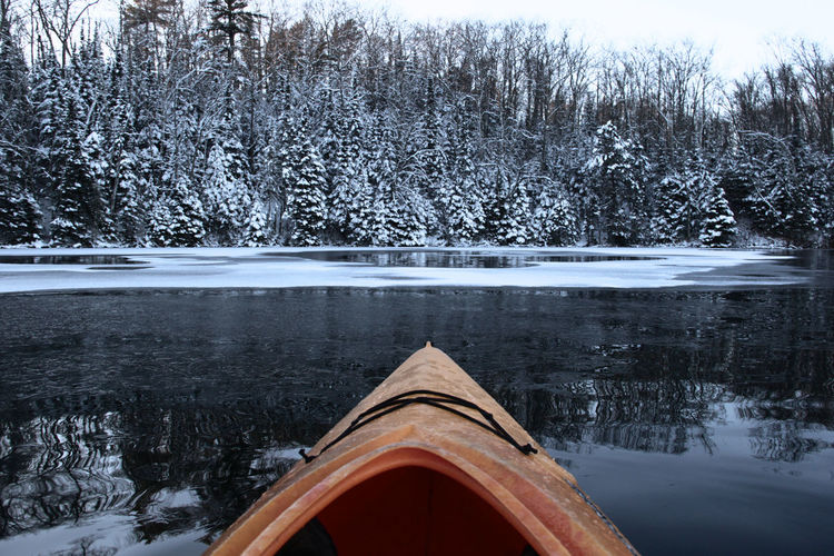 Boat in lake against bare trees during winter