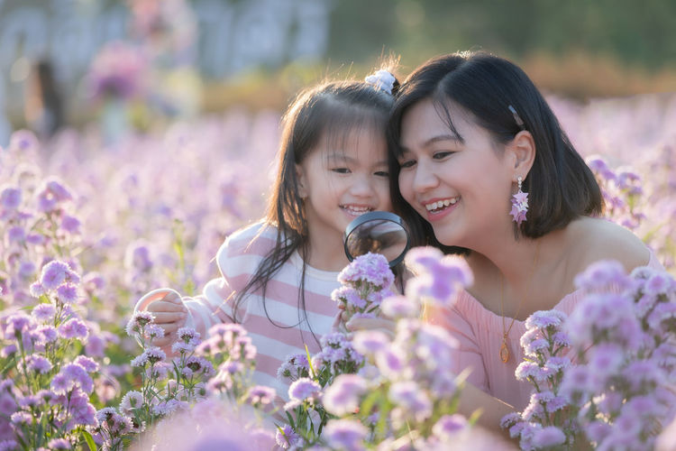Close-up of mother and daughter by purple flowering plants