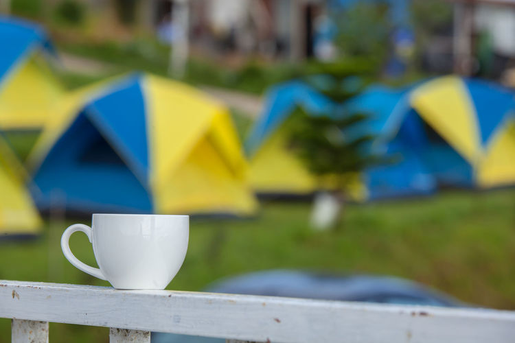 Close-up of cup on railing at campsite