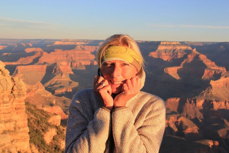 Portrait of woman standing against rocky mountains at grand canyon national park
