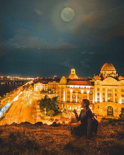 Woman sitting at illuminated park against sky at night