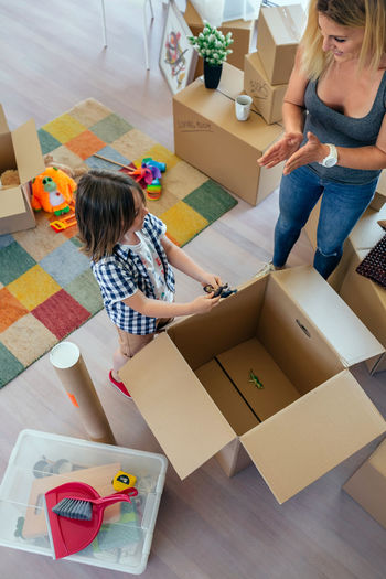 Aerial view of unrecognizable mother and son unpacking moving box Family Fun Happiness Happy Kids Mother Moving Unpacking Woman Apartment Boxes Boy Cardboard Home Interior House Indoors  Lifestyles Living Room New Home Packing Placing Playing Real People Relocating Vertical
