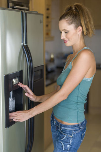 Woman filling glass at the water dispenser of the refrigerator 20-25 Years Old Refreshment Adult Appliance Beautiful Woman Casual Clothing Cold Drink Domestic Life Domestic Room Glass Hairstyle Home Household Equipment Indoors  Kitchen Lifestyles One Person Refrigerator Side View Smiling Standing Three Quarter Length Water Dispenser Women Young Adult