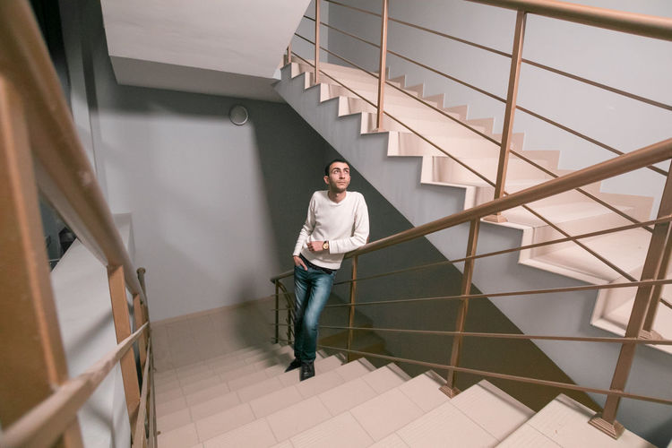 Young man standing on staircase