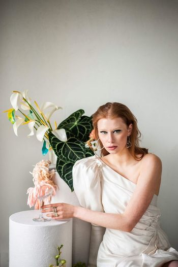Portrait of a young woman sitting on white wall