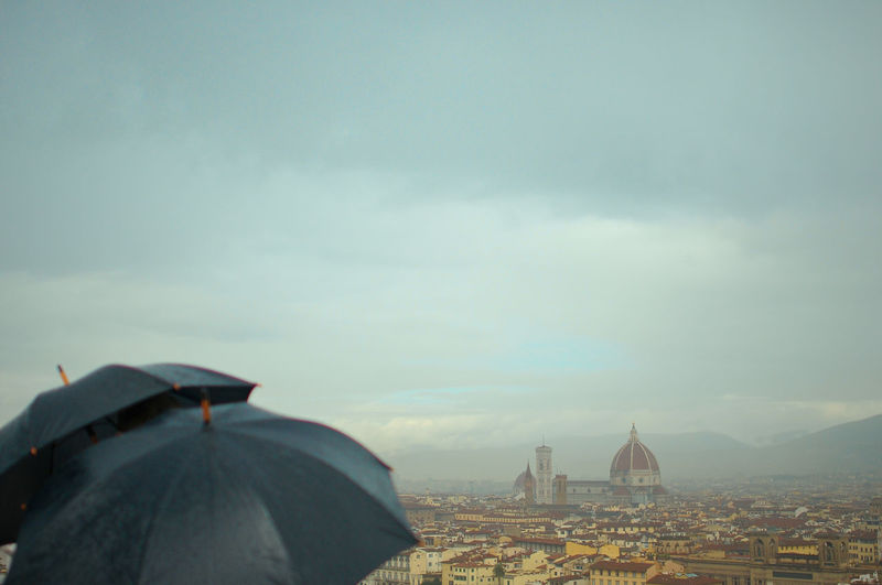 Umbrellas During Rainy Season With Florence Cathedral In Background Against Sky