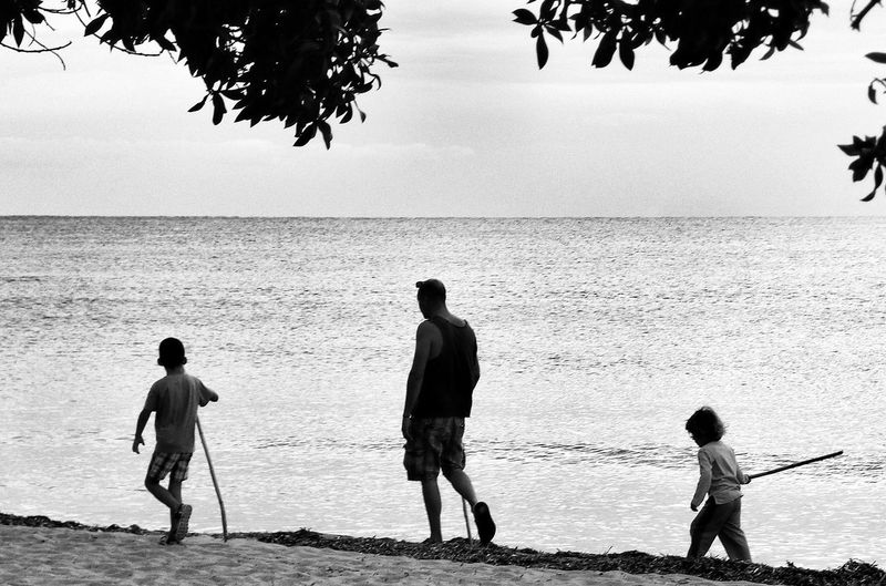 Father And Sons Walking By River Against Sky