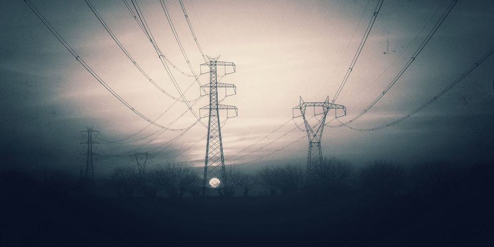 Low angle view of electricity pylon against sky at dusk