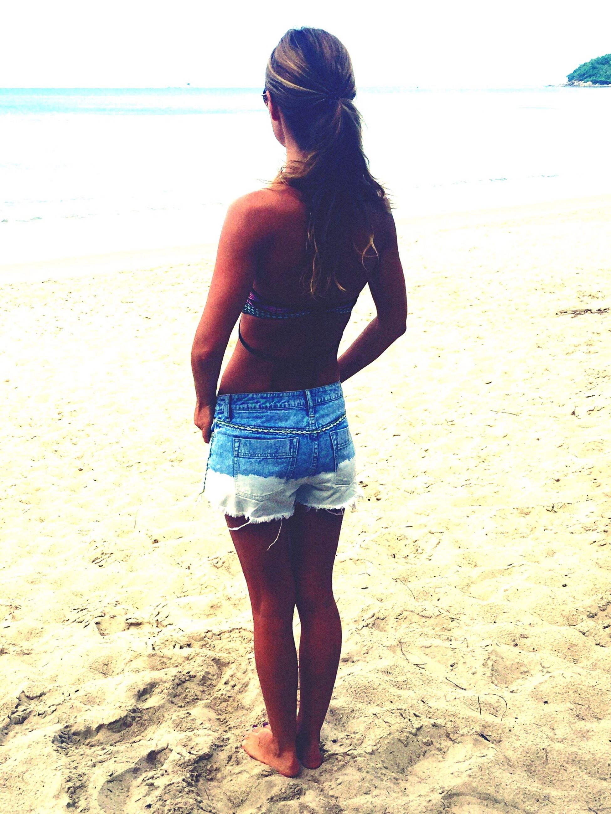beach, sand, sea, shore, young adult, lifestyles, full length, leisure activity, casual clothing, standing, water, young women, person, horizon over water, vacations, rear view, long hair, sunglasses