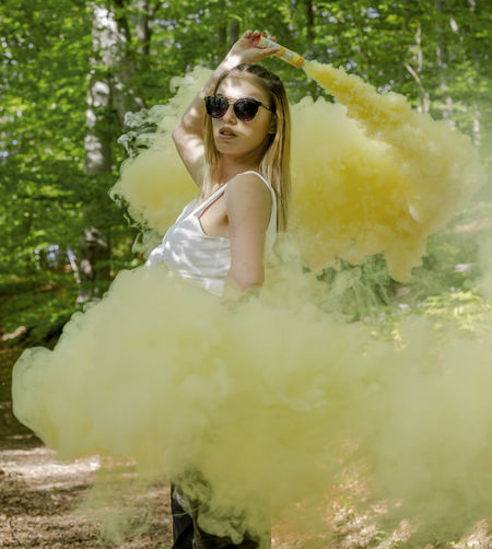 Smoke Smoke Bomb Women One Person Young Women Real People Young Adult Beauty Looking At Camera Hair Adult Beautiful Woman Portrait Lifestyles Leisure Activity Fashion Three Quarter Length Females Standing Nature Hairstyle Outdoors