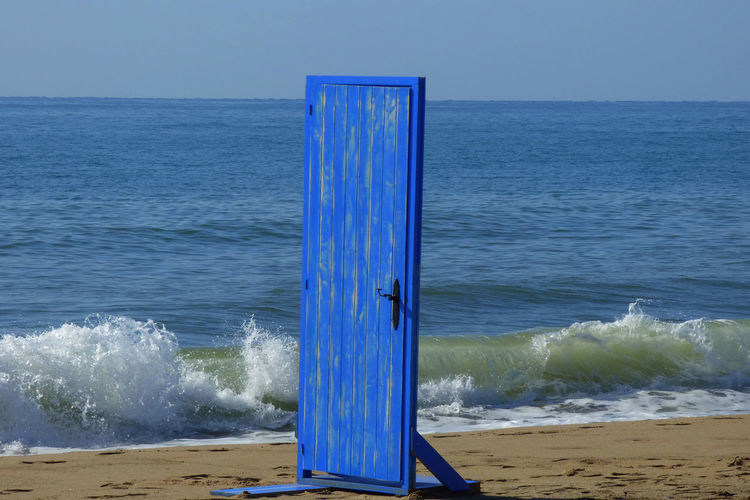 Beach Beauty In Nature Blue Clear Sky Day Door Door On The Beach Horizon Horizon Over Water Land Motion Nature No People Outdoors Scenics - Nature Sea Sky Tranquil Scene Tranquility Water Wave Wooden Post