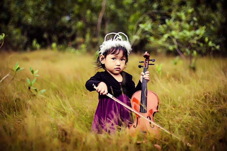 Girl playing violin on grassland
