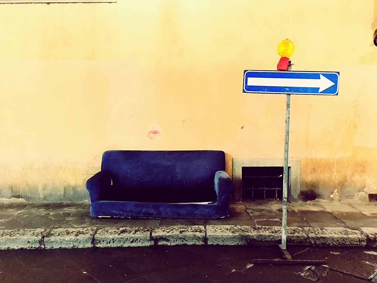 yellow, sign, no people, communication, wall - building feature, architecture, seat, built structure, empty, absence, guidance, arrow symbol, wall, day, chair, outdoors, road, information, road sign, nature
