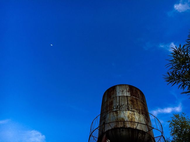 The old water tank, the moon and the blue sky Rusty Rusty Water Tank Water Tank Blue Sky Half Moon Sky Blue Low Angle View Architecture Built Structure Tree Nature Cylinder Clear Sky Visual Creativity