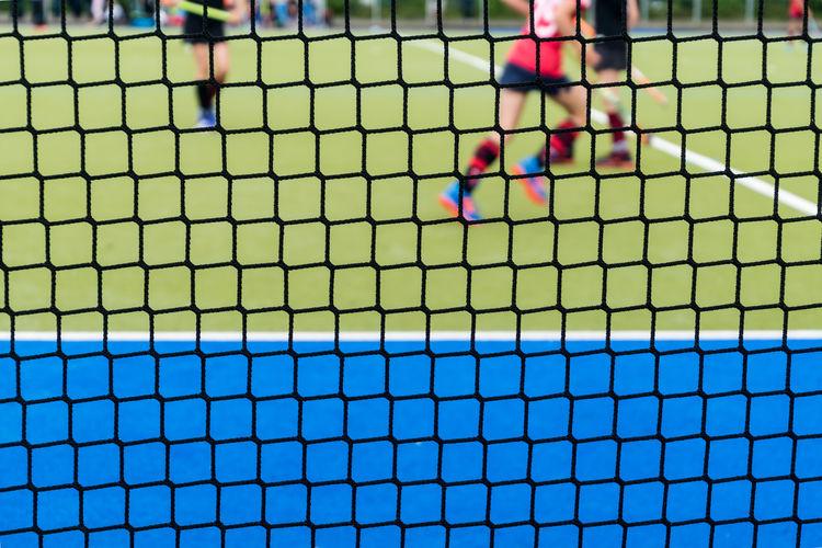 Players playing hockey seen through net