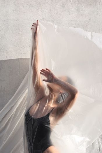 Woman with arms raised covered in plastic