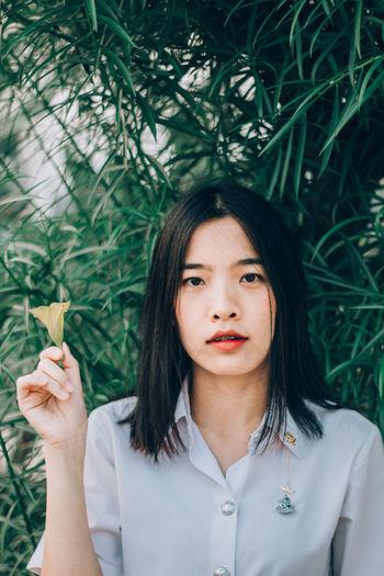 Portrait of beautiful woman holding flower against plants