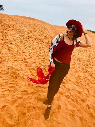 Woman wearing sunglasses looking away standing at desert against sky