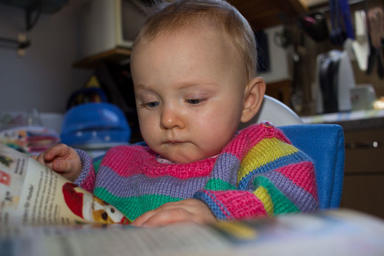 Cute baby girl reading while sitting at home