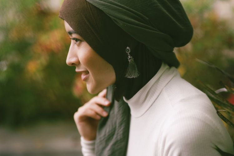 Close-up of smiling woman wearing hijab standing outdoors