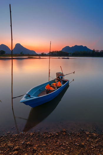 Fisherman Boat At Lake With Mountain Background During Morning Beauty In Nature Blue Boat Clear Sky Fish Fishing Hill Lake Mode Of Transport Morning Mountain Mountain Range Nature Nautical Vessel Orange Color Perlis Silkywaters Smooth Standing Water Sun Timah Tasoh Tranquil Scene Tranquility Transportation Water