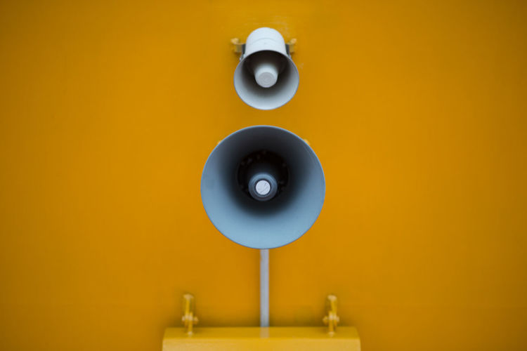 Close-up of loudspeaker on yellow wall