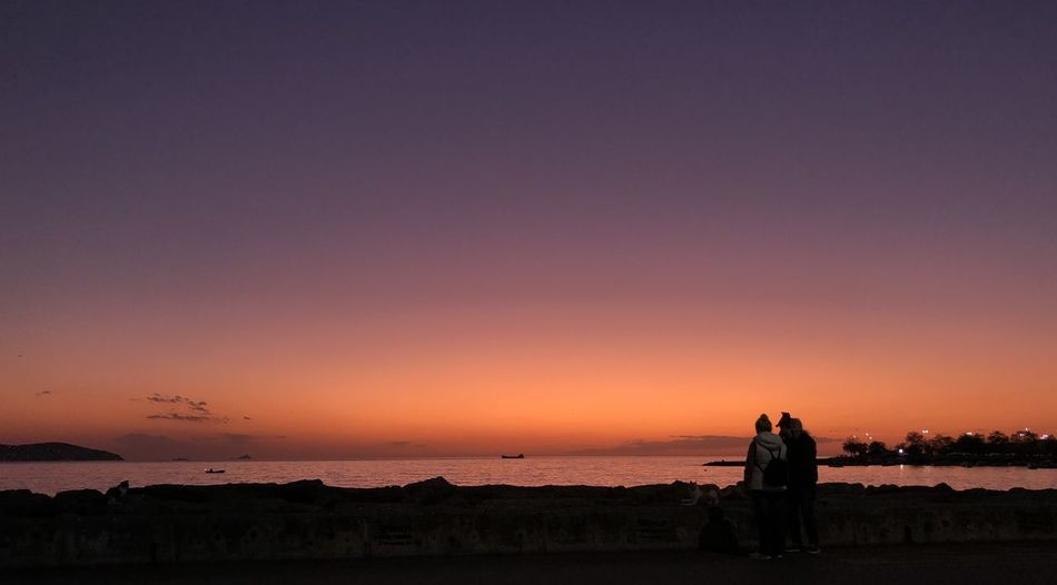 Male and female sitting by sea against sky during sunset