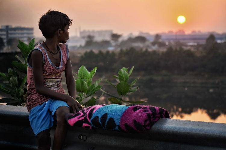 Child sitting and watching sunset