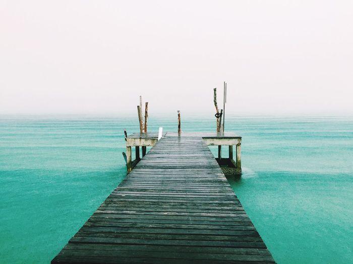 Wooden pier on calm sea against clear sky