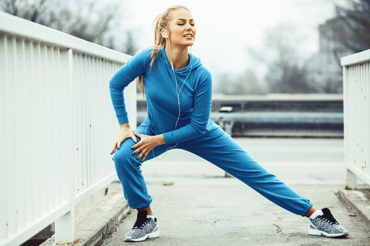 Full Length Of Woman Listening Music While Exercising On Footpath