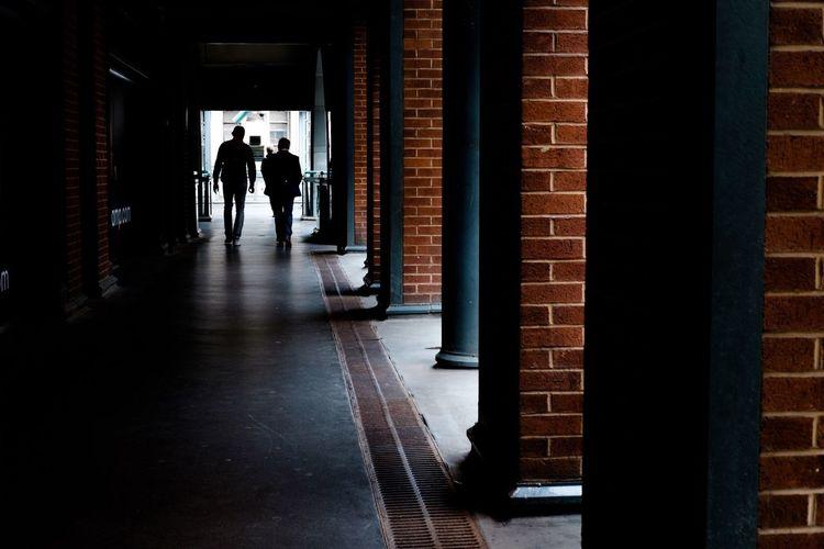 Rear View Of Silhouette Men Walking In Colonnade