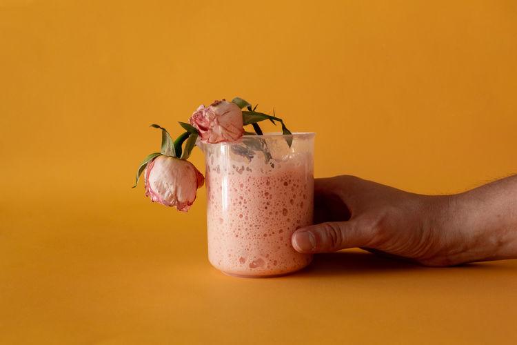 Close-up of hand holding drink against orange background