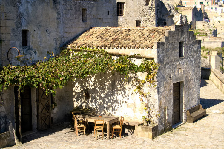 Ancient stone house with grapes tree and old wooden tables and chairs overlooking the canyon of the sassi or stones of Matera European capital of culture 2019, Basilicata, Italy Day Nature Architecture Outdoors Matera Basilicata Italy Sassi Di Matera Capital Of Culture 2019 Wooden Table Old Ancient Hystorical Heritage Typical Traditional Grapes House Old House Stone Old Roof Rocks Canyon History
