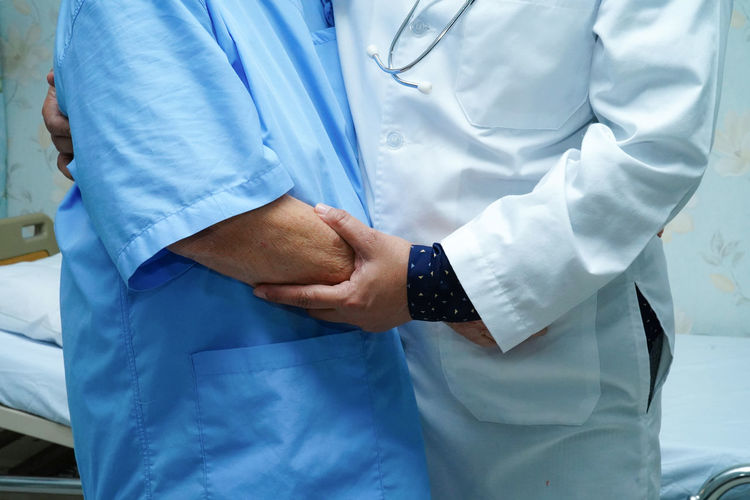 Midsection of doctor embracing patient while standing in hospital