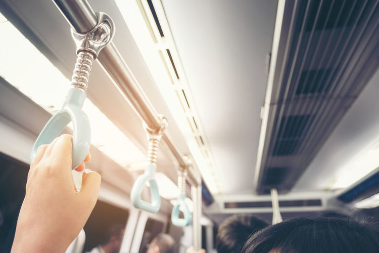 Passenger hand holding onto a handle of a train on blur background, Woman holding onto a handle on a train Human Hand Human Body Part Mode Of Transportation Hand Real People Vehicle Interior Transportation Travel Airplane Public Transportation Air Vehicle Holding Body Part Rail Transportation Close-up Women People Indoors  Focus On Foreground Ceiling Finger