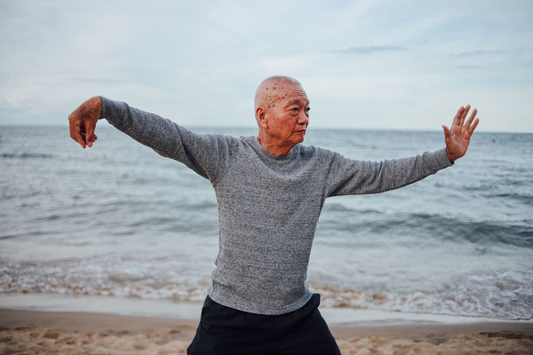 Senior man exercising while standing at beach against cloudy sky during sunset