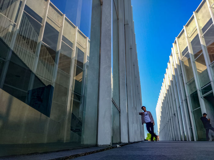 Low angle view of man standing amidst buildings in city