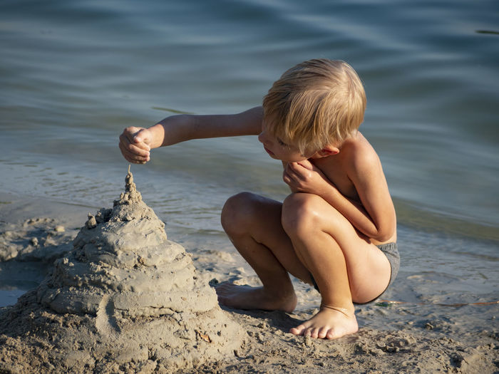 Cute boy making sandcastle at lakeshore