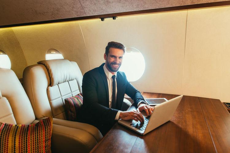Smiling businessman using laptop in airplane