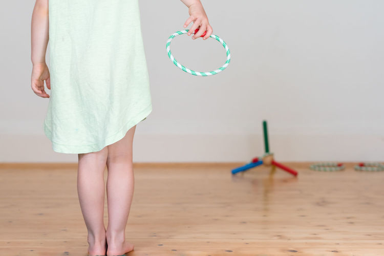 Low Section Of Girl Holding Ring While Playing At Home