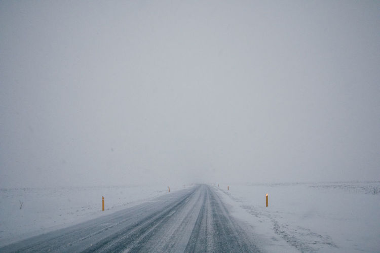 Road amidst snow covered field against sky