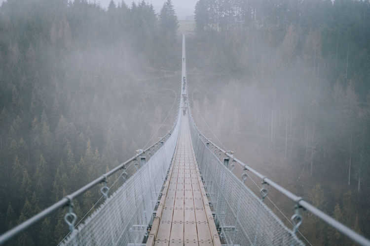 Famous Geierlay Bridge in Germany in Winter. Fog The Way Forward Bridge Rope Bridge Bridge - Man Made Structure No People Outdoors Forest Tranquility Direction Nature Footbridge Germany GERMANY🇩🇪DEUTSCHERLAND@ Geierlay Geierlay Hängebrücke Hunsrück Nature Eifel Tower Deutschland Beauty In Nature
