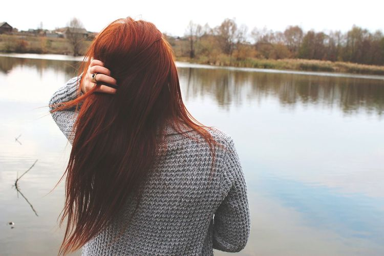 Rear view of redhead woman by lake