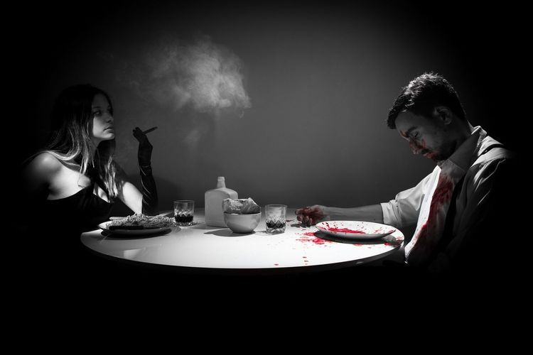 Woman smoking while having food in front of dead man