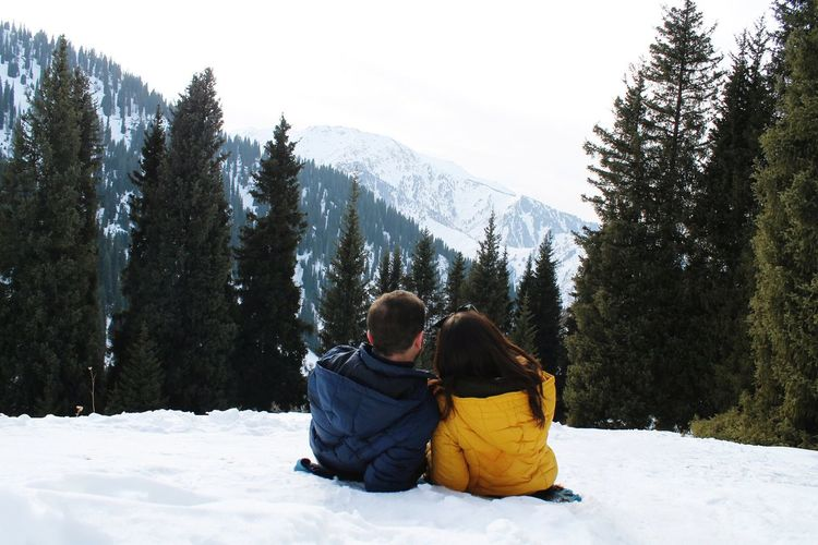 Rear view of couple lying on snow covered mountain against sky