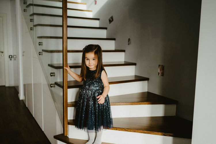 Portrait of woman standing on staircase at home
